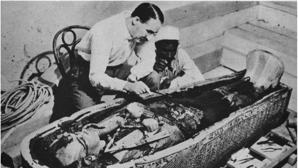Carter lehnt über dem geöffneten Sarg von Tutanchamun