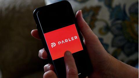 Auf einem Handy wird das Logo der Social-Media-Plattform Parler angezeigt