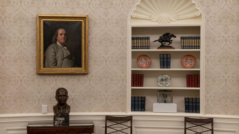 Auf einem Tisch im Oval Office steht eine Büste von Harry Truman, an der Wand hängt ein Bild von Benjamin Franklin.