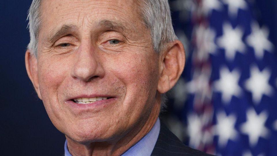 Vor einer US-Flagge sitzt ein weißhaariger Mann im Anzug und lächelt