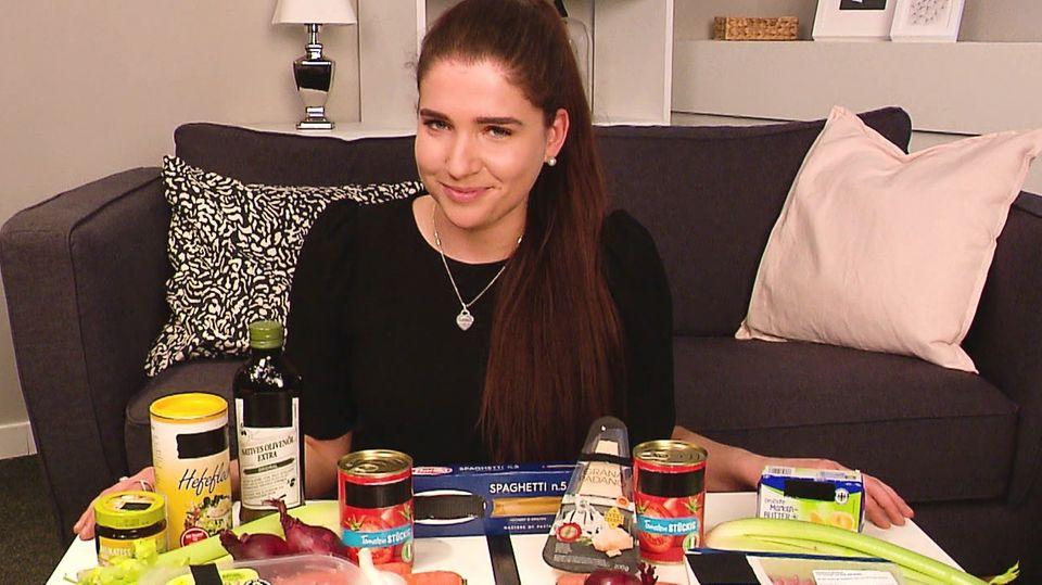 RTL-Reporterin Elena Rosemeyer hat vor ihr auf dem Tisch verschiedene vegane Lebensmittel