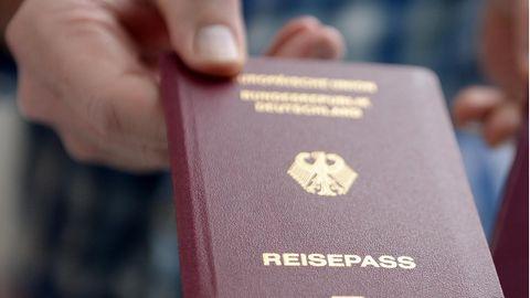 """Eine rechte Hand hält einen weinroten Reisepass mit goldenem """"Bundesrepublik Deutschland"""" in die Kamera"""