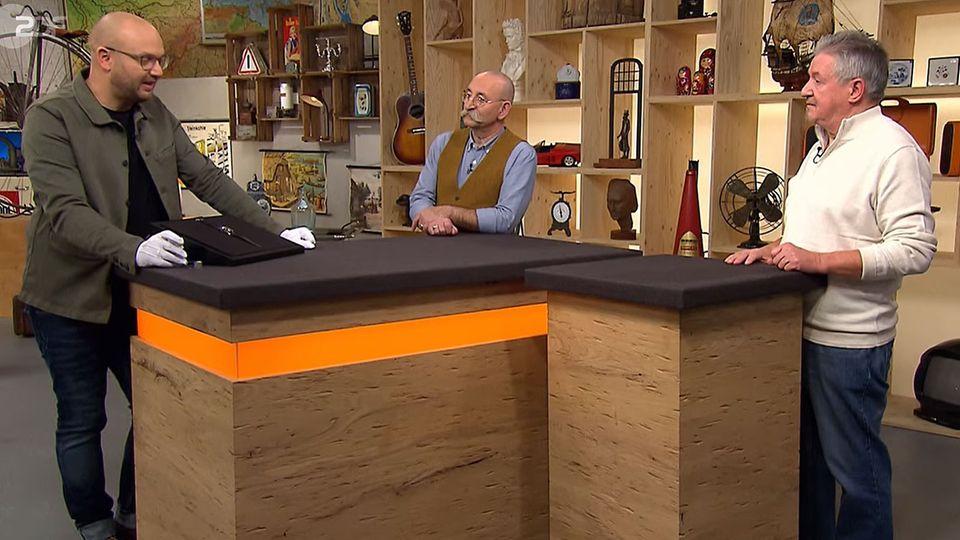 """""""Bares für Rares""""-Experte Sven Deutschmanek erklärt Moderator Horst Lichter die Uhr von Besitzer Franz Spiess."""