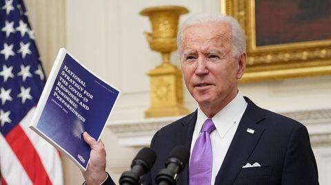 An einem Rednerpult mit Wappen des US-Präsidenten steht Joe Biden und hält mit Rechts ein Strategiepapier gegen Corona hoch