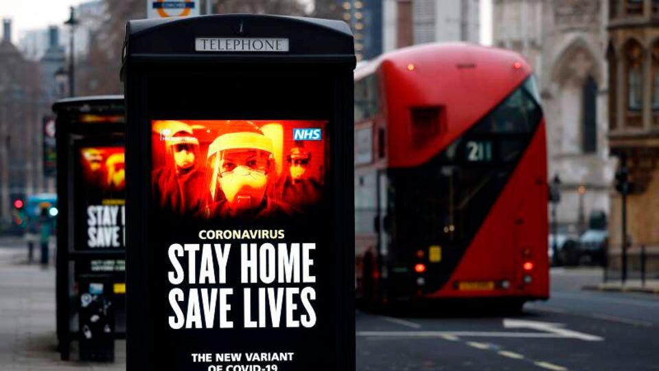 Ein Plakat mit Maßnahmen gegen das Coronavirus in London, daneben ein roter Bus