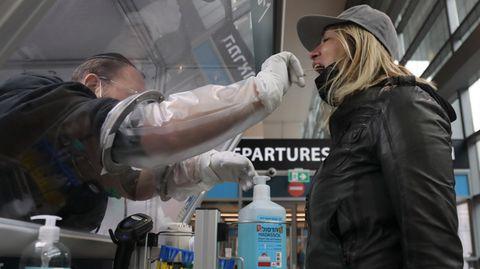Ein Mitarbeiter des Flughafens Ben Gurion International Airport in Tel Aviv entnimmt einer Passagierin eine Probe für einen Corona-Schnelltest.