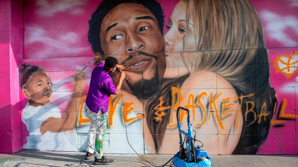 Los Angeles, Vereinigte Staaten. Der US-amerikanischer Basketballspieler Kobe Bryant und seine Tochter Gianna kamen am 26. Januar 2020 bei einem Hubschrauberabsturz ums Leben. In Erinnerung an beide schafft der Künstler Artist Tehrell zum Jahrestag des Unglücks ein Wandgemälde.
