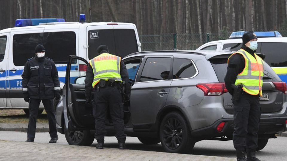 Polizisten der Landespolizei kontrollieren vor dem Grenzübergang Ahlbeck ein Fahrzeug, das in Richtung Polen unterwegs ist.