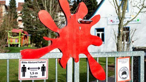 """Ein Schild mit der Aufschrift """"Bitte Abstand halten!""""hängt am Tor eines Kindergartens, der nur noch für Notbetreuung geöffnet ist."""