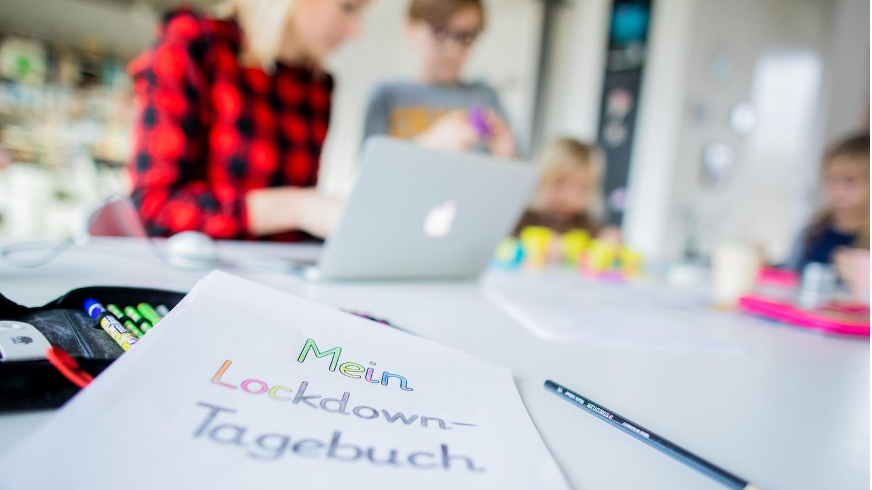 Eine Lehrerin sitzt mit ihren drei Kindern im Wohnzimmer undunterrichtet ihre Schüler im Distanzunterricht