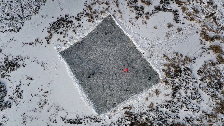 Farbklecks auf einer vom Schnee freigeräumten Eisfläche in Ruderatshofen, Bayern, mit einemrot gekleideten Schlittschuhläufer