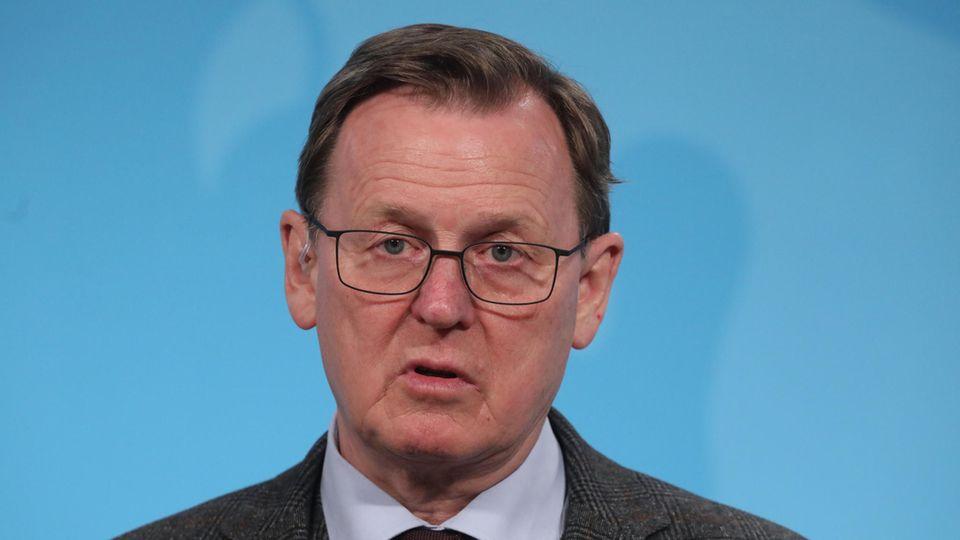 Bodo Ramelow - ein Mann mit Brille und dunkelblondem Seitenscheitel -  spricht vor einer blauen Wand in ein Mikro des MDR