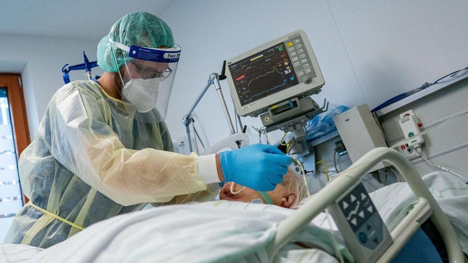 Eine Pflegekraft in voller Schutzausrüstung kümmert sich um einen älteren, weißhaarigen Mann, der in einem Bett beatmet wird