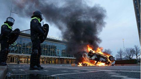 Flammen schlagen aus einem Auto, das vor dem Bahnhof in Eindhoven auf dem Kopf liegt