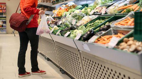 Eine Kundin steht in der Obst- und Gemüseabteilung in einem Supermarkt