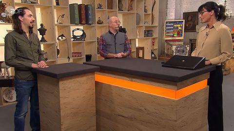 Bares für Rares: Besitzer Freyer. Moderator Horst Lichter, Expertin Heide Rezepa-Zabel stehen am Tisch