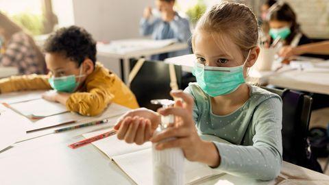 Kinder in einem Klassenzimmer mit Masken und Desinfektionsmittel