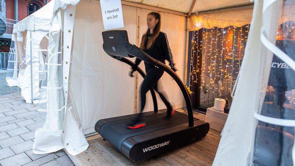 In einem weißen Party-Pavillion trainiert eine junge Frau ganz in Schwarz auf einem Laufband