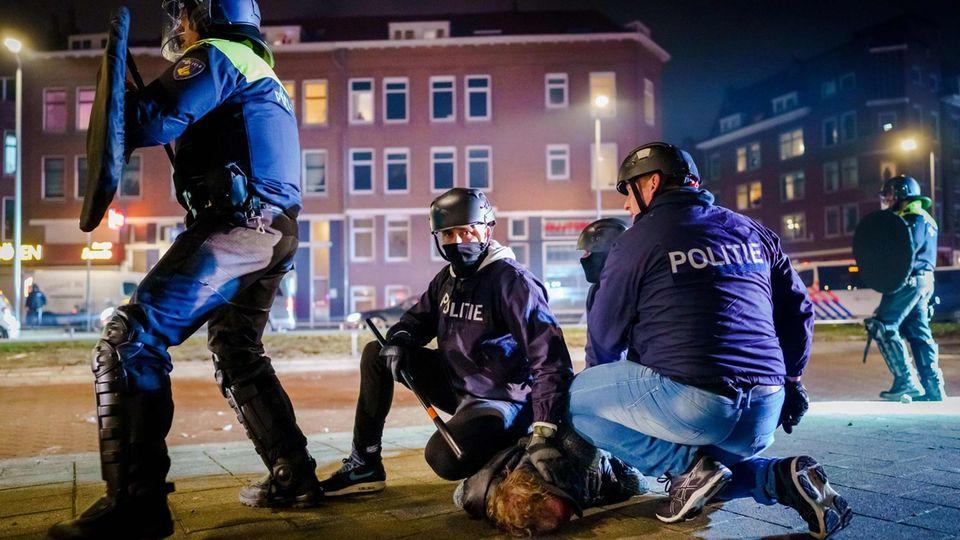 Drei Polizisten halten einen Mann am Boden, während ein vierter Polizist die Kollegen mit Schlagstock und Schild schützt