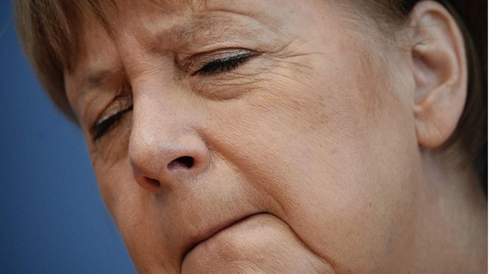 Angela Merkel mit verkniffenem Gesichtsausdruck