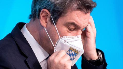 Bayerns Ministerpräsident Markus Söder ist im Profil zu sehen, während er seine FFP2-Maske mit Landeswappen richtet
