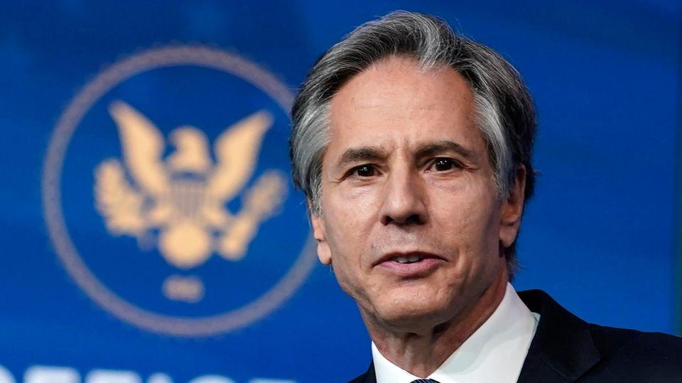 Ein weißer Mann mit grau meliertem Seitenscheitel steht im Anzug vor einer blauen Wand mit goldenem Wappen der USA