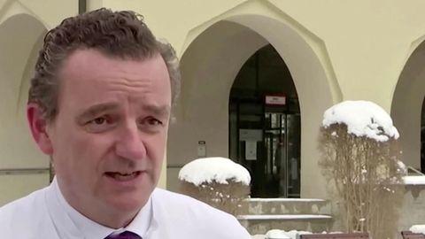 Ein Mann im weißen Kittel und rot-blau gestreifter Krawatte lächelt sanft. Er hat dunkelblonde, gegelte Locken und braune Augen