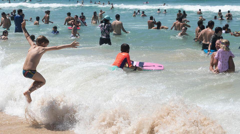 Eine etwa achtjähriger Junge in Badeshorts springt am Strand über eine brechende Welle. Im Wasser sind schon viele Erwachsene