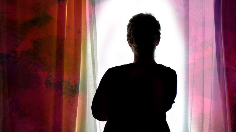 Eine Frau steht vor dem Fenster und schaut hinaus, man sieht sie von hinten im Schatten