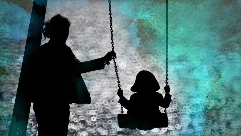Eine Frau schaukelt ihr Kind, man sie die beiden von hinten im Schatten