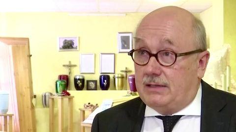 Ein Mann mit grauer Halbglatze und brauner Hornbrille steht im Anzug vor einer Wand voller Särge und Urnen