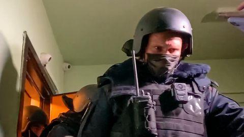 Ein Polizist mit Helm und Schutzweste geht in dunkelblauer Uniform nach einer Razzia die Treppe vor einer Wohnungstür herunter
