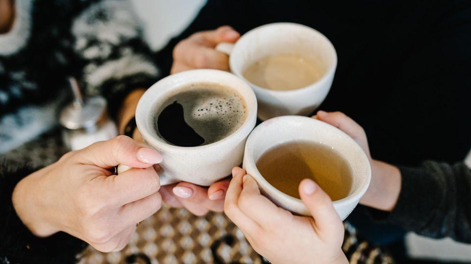 Hände halten Tassen mit Kaffee und Tee