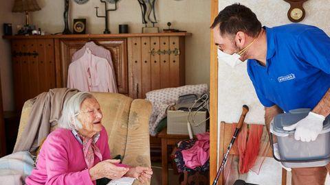 Pfleger Ingo Tropartz unterhält sich mit alter Frau im Sessel