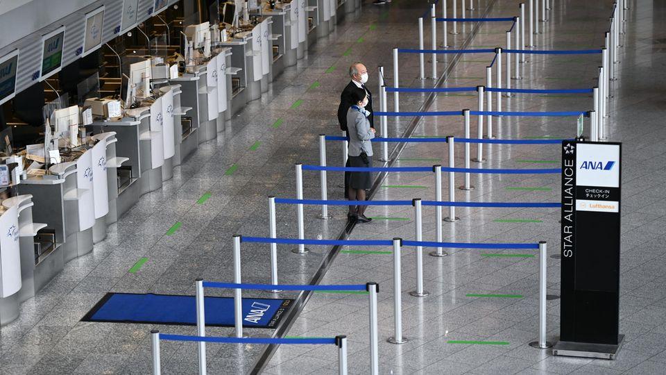 Mitarbeiter einer Fluggesellschaft stehen vor leeren Abflugschaltern am Frankfurt Airport
