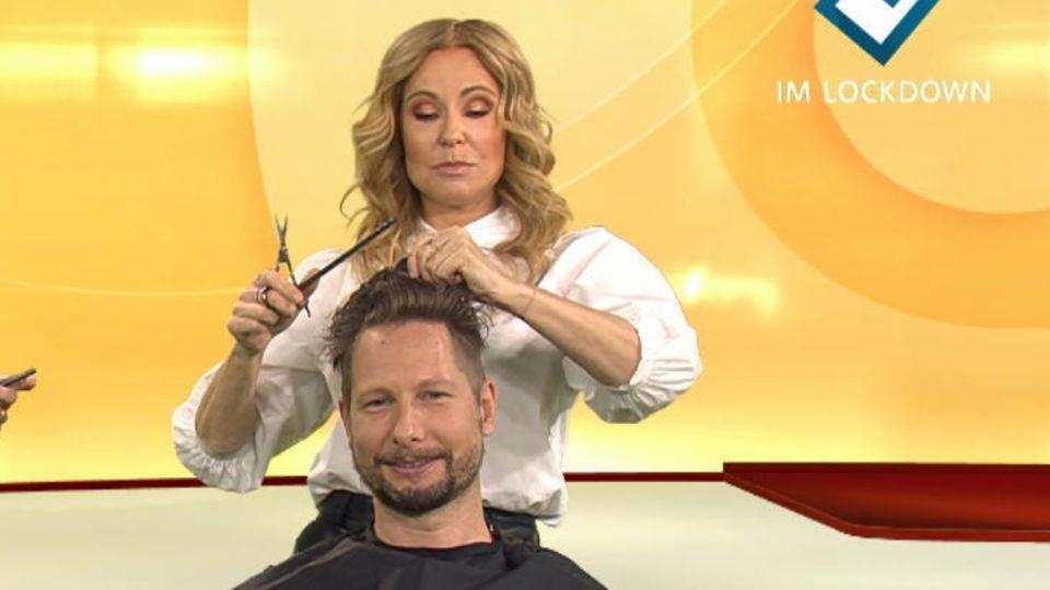 Katja Burkard schneidet einem Reporter die Haare