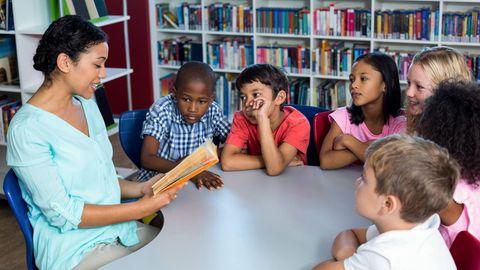 Eine Lehrerin liest einer Gruppe Kindern ein Buch vor
