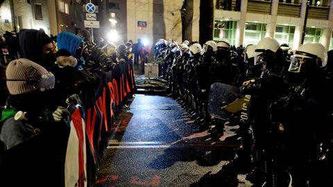 Links steht alles voller Demonstranten, die hinter einem Banner laufen. Wenige Meter vor ihnen steht eine Kette Polizisten