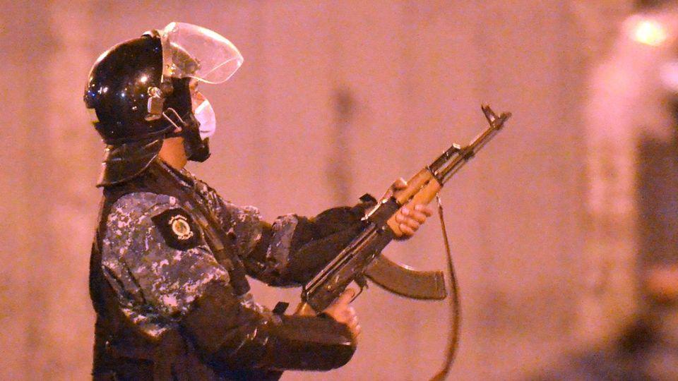 Ein Polizist in Tarn-Uniform und schwarzem Helm schießt mit seinem Gewehr im 45-Grad-Winkel nach oben