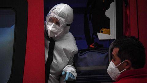 Eine Pflegekraft schaut in weißem Vollschutz-Anzug aus der Schiebetür eines roten Rettungswagen, der vor Santa Maria Hospital