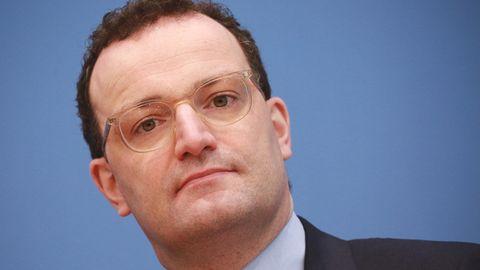 Vor einer blauen Wand legt Bundesgesundheitsminister Jens Spahn seinen Kopf schräg. Er hat braune Locken, trägt Anzug und Brille