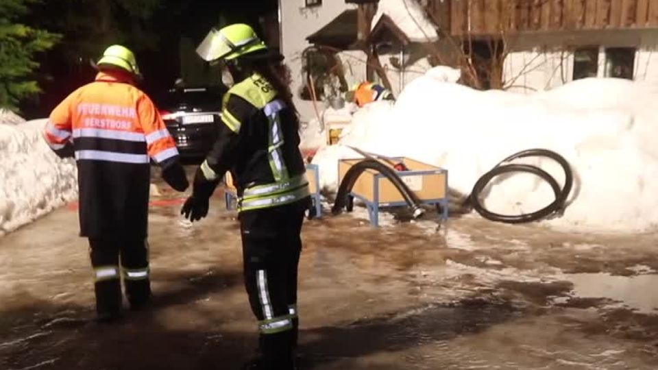 Zwei Feuerwehrleute stehen auf einer Straße bis zu den Knöcheln im Hochwasser. Hinter ihnen ein hoher Schneehaufen