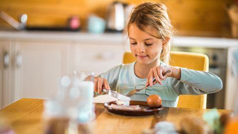 Ein Mädchen sitzt am Tisch und isst