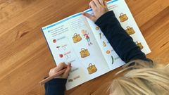 Schreiben und Lesenlernen in der ersten Klasse. Der Sechsjährige braucht noch viel Motivation. Er kann vieles schon allein, möchte aber, dass jemand bei ihm sitzt.