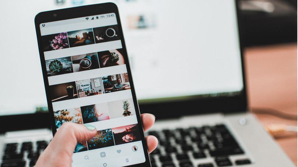 Eine Frau scrollt auf dem Handy durch Instagram