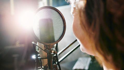 Eine Person sitzt vor einem Radio-Mikrofon