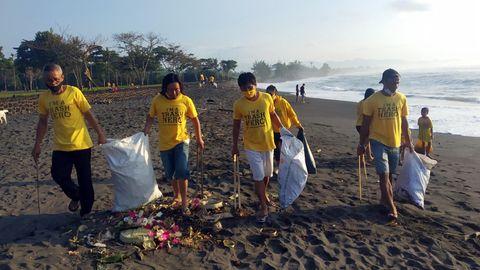 Am Saba Beach auf Bali: Teilnehmer einer Müllsammelaktionen von Trash Herosammeln an einem Strand mit langen Zangen Unrat auf.