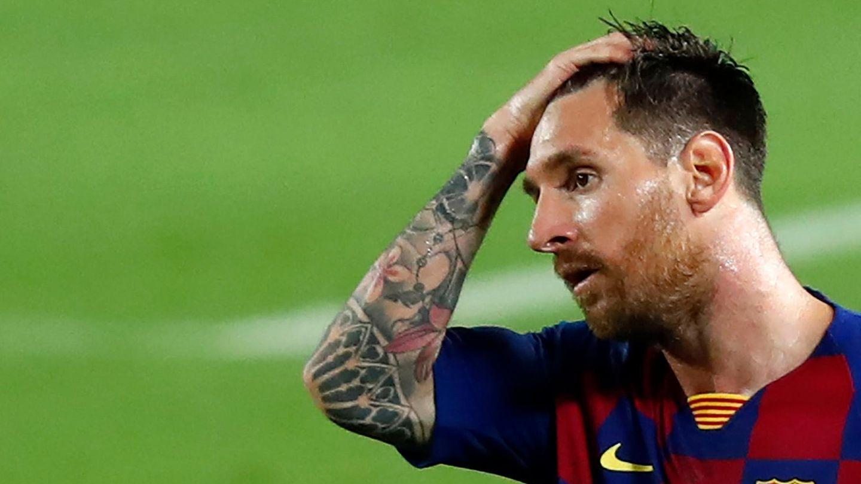 Lionel Messi steht im rot-blau karierten Trikot des FC Barcelona auf dem Rasen und streicht sich mit rechts durch die Haare