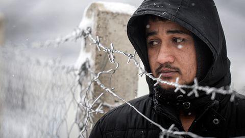Ein Migrant steht bei Schneefallin derbosnischen Stadt Velika Kladusanahe der Grenze zuKroatien an einem Stacheldrahtzaun