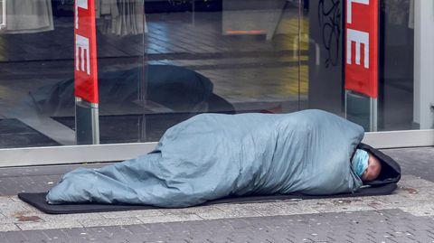 Ein Obdachloser vor einem Modegeschäft in Köln